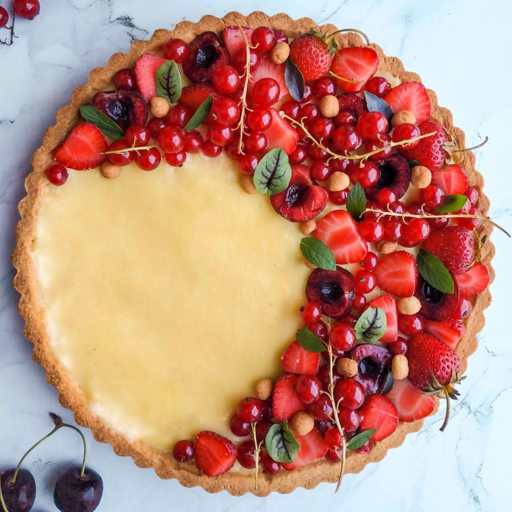 Fresh fruit tart with cream and berries