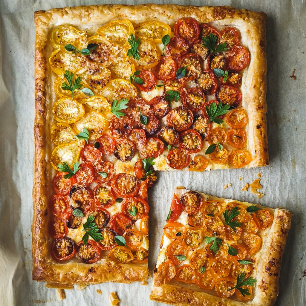 Puff pastry tart with cheese and multi colored tomatoes.