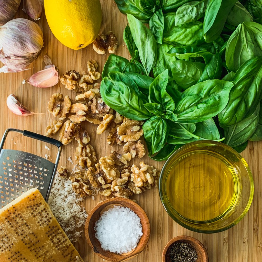 Assembled pesto ingredients on a board.