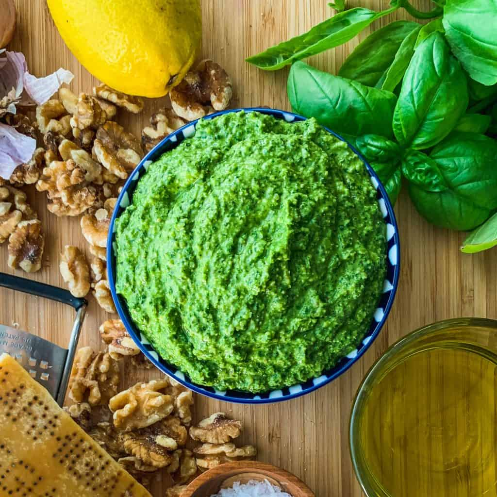 Finished pesto in serving bowl sitting on a cutting board with loose ingredients.