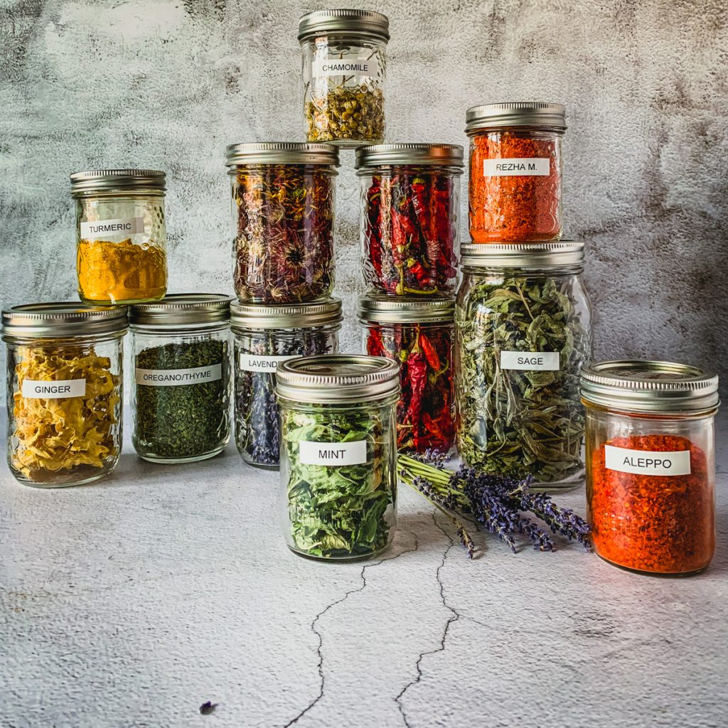 herbs and peppers stored in mason jars.