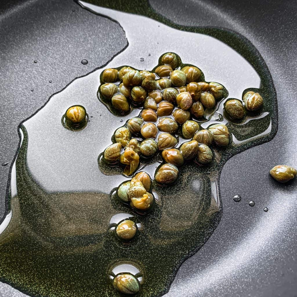 Capers and oil in a frying pan.